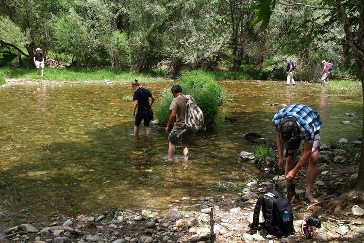 groepje wandelaars waadt blottsvoets naar de overkant van een riviertje